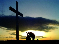 A picture of a man kneeling before a cross